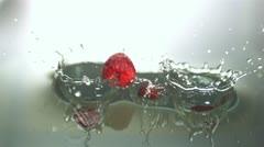 Raspberries falling in water Stock Footage