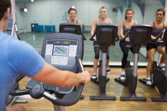 Man teaches spinning class to happy women - stock photo