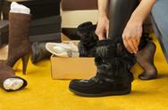 Women fit on boots near heap of shoes boxes Stock Photos