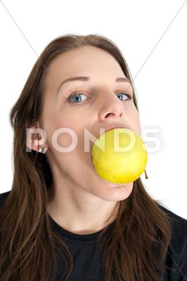 Stock photo of woman biting a yellow apple