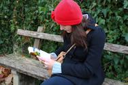 Woman sitting on a bench and reading a book Stock Photos