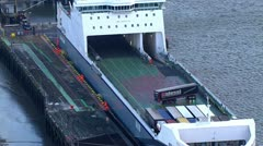 Truck drivers manoeuvring their vehicles into position on a container ship Stock Footage