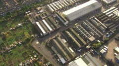 Aerial view over fields and hedgerows and industrial buildings in England Stock Footage