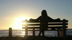 Girl On Bench, Overlooking Ocean at Sunset - stock footage