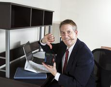 Mature man giving thumbs down on income tax results Stock Photos