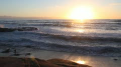 Waves roll in to a beautiful beach at Sunset - stock footage