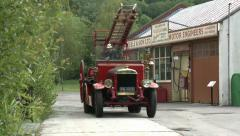 Vintage Fire Engine Driving Past Old Garage With Bell Ringing Stock Footage