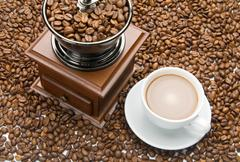 Old coffee grinder and a cup of coffee Stock Photos