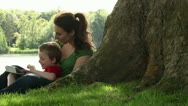 Stock Video Footage of Mum and son playing on tablet by tree