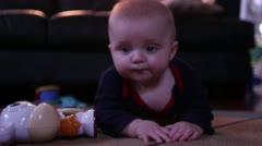 6 month male caucasian baby playing on carpet with light up toy Stock Footage