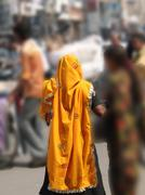 hindu woman in bright orange scarf visits the lad bazaar .. - stock photo