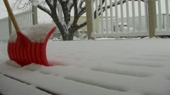SNOWING lightly on porch w/ snow shovel - stock footage
