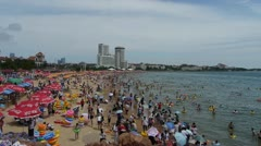 A lot of people at crowded bathing sandy beach.People swim in sea,QingDao. Stock Footage