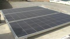 Solar panel pan reveal to Greek village Medium shot Stock Footage
