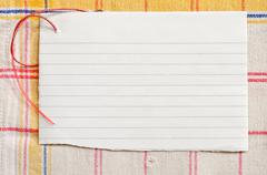 Torn lined paper with red wire on old tablecloth, horizontal shot Stock Photos