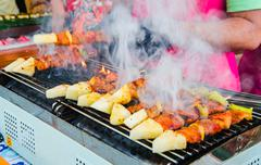 Bbq chicken and pork on a stick with peper and pineapple on stove Stock Photos