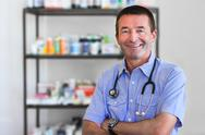 Mature doctor standing in front of medicine Stock Photos