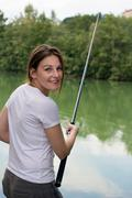 woman fishing at a lake - stock photo