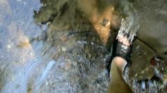 Leg flip-flop shoes walk imitation park brook stream water flow Stock Footage