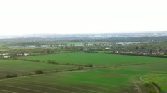Aerial shot over lush green fields and meadows in the English countryside Stock Footage