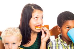 woman with kids eating pizza - stock photo