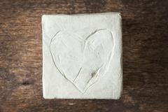 square with clay heart on wooden surface - stock photo