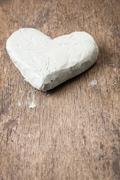 clay heart on wooden surface - stock photo