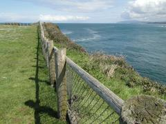 Wooden fence on rocky headlands and surf .. Stock Photos