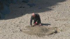Man Digging Sandcastle Stock Footage