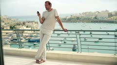 Young man using cellphone on the terrace Stock Footage