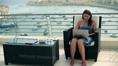 Happy woman sitting on the terrace and finish working on laptop computer Stock Footage