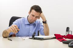 young stressed manager analyzing some charts - stock photo