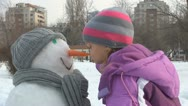 Stock Video Footage of Little Girl Playing with Snowman, Smiley Child in Snow, Children in Park, Winter