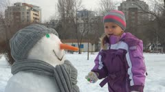 Child Finishing a Snowman, Little Girl Playing In Park, Winter Games, Children Stock Footage
