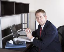 Mature man not happy working on personal income taxes Stock Photos
