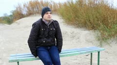 A young man is sitting on the bench and looking at the sea. Stock Footage