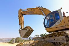 back hoe vehicle on a pile of dirt - stock photo