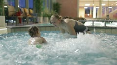 Young mother is playing with her son in the pool of the spa-salon. Stock Footage