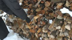 Woman arrange wood chips for winter time rural countryland farm snow yard cold Stock Footage