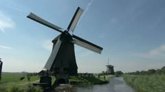 Netherlands Kinderdijk windmill turning above outflow into canal 10 Stock Footage