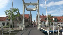 Netherlands Edam bikes cross canal under bridge frame Stock Footage