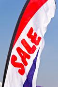 Stock Photo of sale flag flying against blue sky