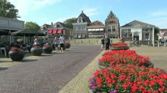 Netherlands Edam red flowers in round planters on square Stock Footage