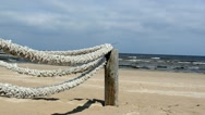 Fence wooden log thick rope tie beach seaside sea wave Stock Footage