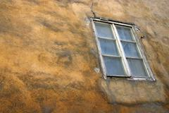 spotted wall with window on alleyway - stock photo