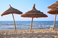 thatched sunshades on the beach - stock photo