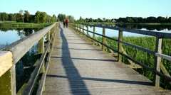 Young couple walk hand in hand on wooden bridge lake Stock Footage