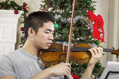 young adult man playing music during the holidays - stock photo