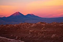 Sunset over volcanoes licancabur and juriques and valle de la luna, atacama d Stock Photos