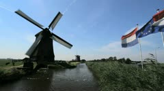 Netherlands Kinderdijk windmill turning and flags in breeze 7 Stock Footage